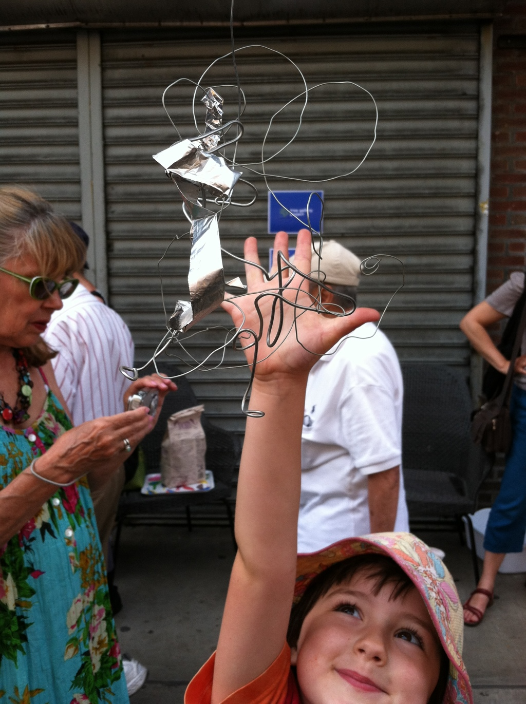 Nina high fives Susan's sculpture with Susan to the left checking email